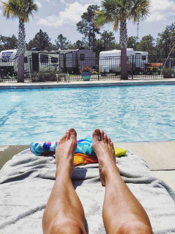 A lady's legs in view, she is relaxing by the Bay Palms RV pool